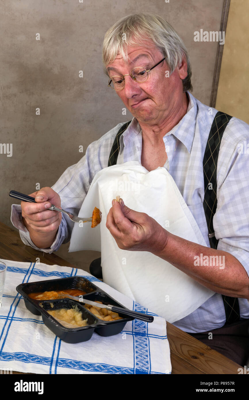 Funny elderly man breaking a tooth while eathing his tv dinner Stock Photo
