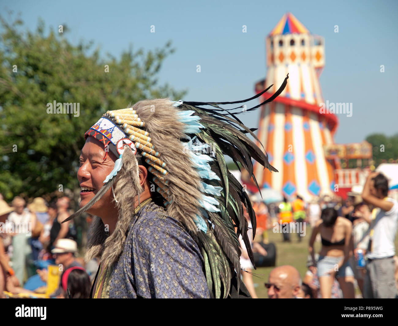 An Indian headdress is worn by a visitor to Love Supreme, an English music festival - Stock Image