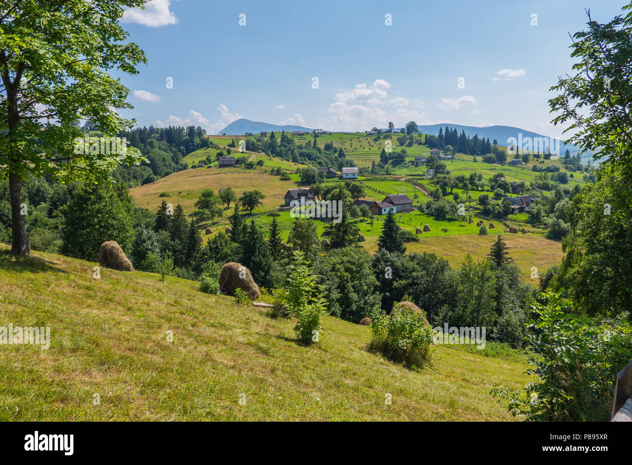A sultry blue sky with rare clouds hung over a small village with beautiful mountain scenery around. . For your design - Stock Image