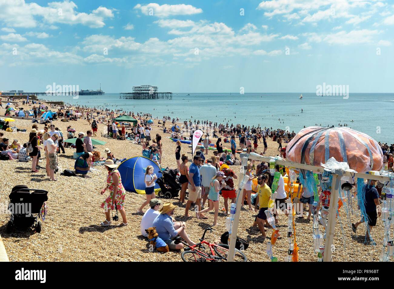 Crowded Brighton beach in the Summer heat - Stock Image