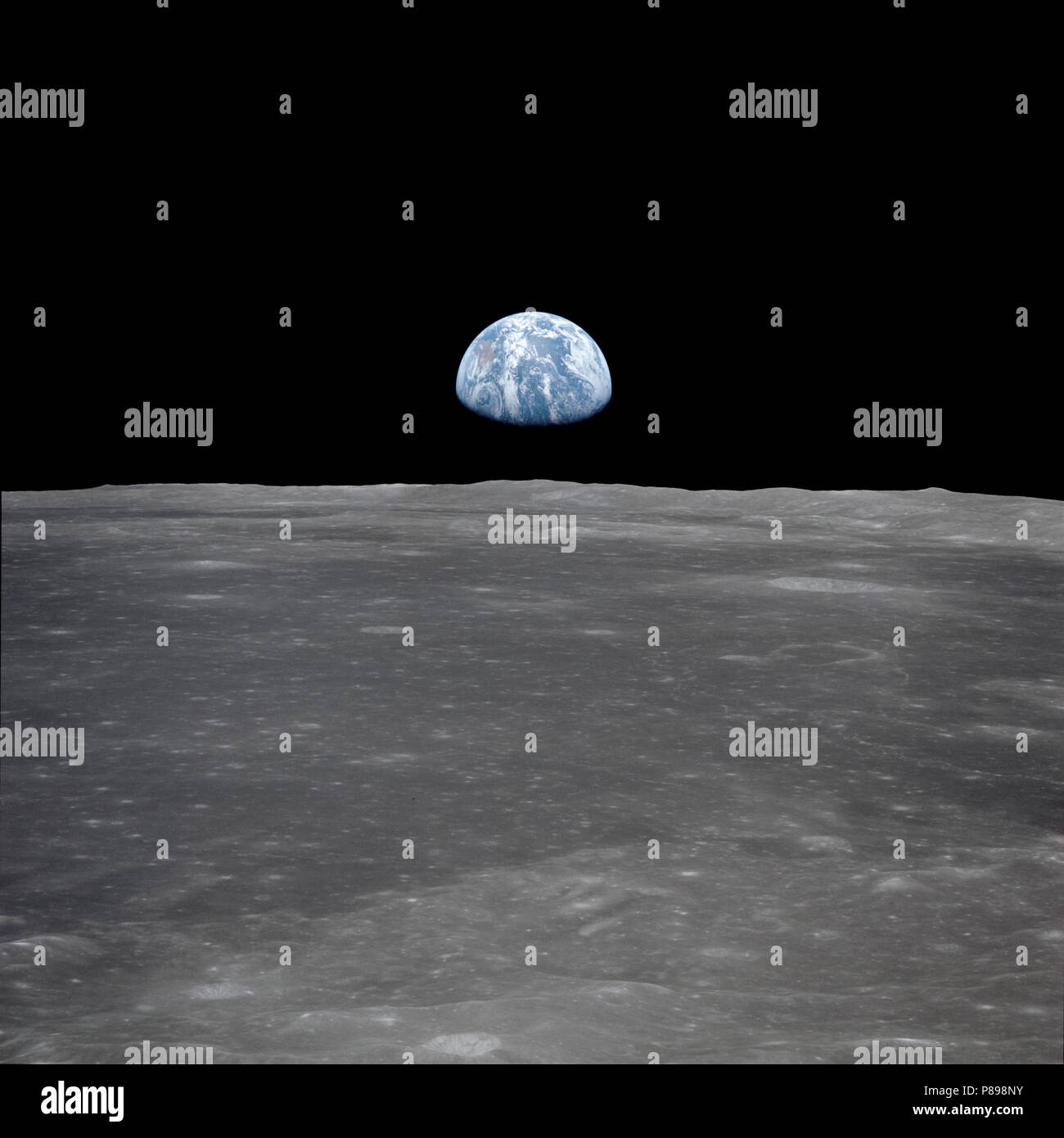 This view from the Apollo 11 spacecraft shows the Earth rising above the moon's horizon. The lunar terrain pictured is in the area of Smyth's Sea on the nearside - Stock Image