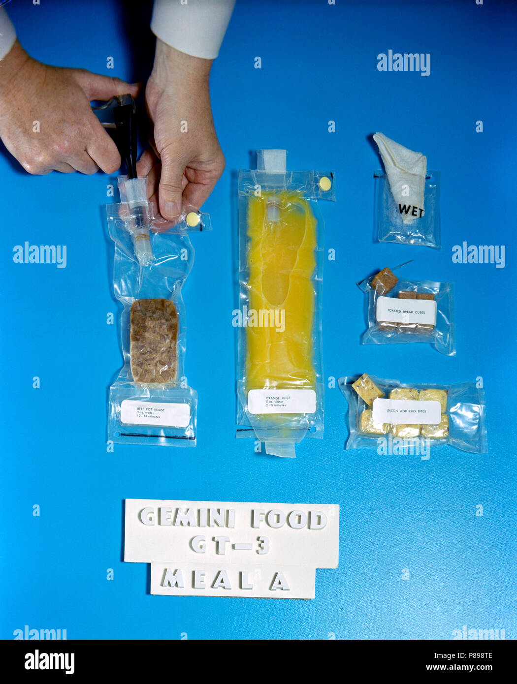 Food packets for use on the Gemini-3 flight including dehydrated beef pot roast, bacon and egg bites, toasted bread cubes, orange juice and a wet wipe - Stock Image