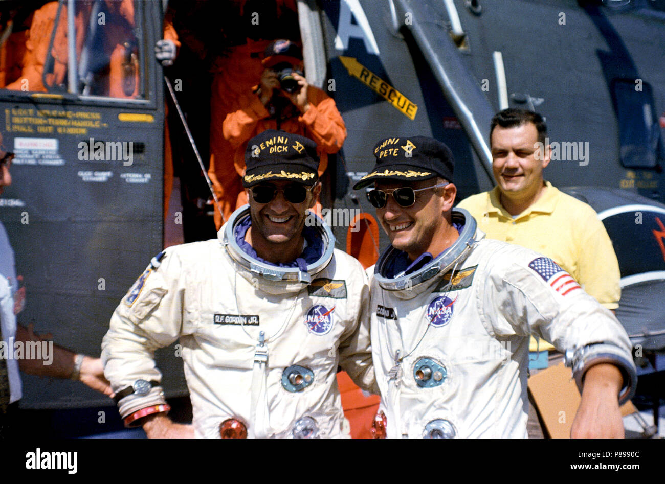 Astronauts Charles Conrad Jr. (right) and Richard F. Gordon, Jr. pose in front of the recovery helicopter which brought them to the U.S.S. Guam Stock Photo
