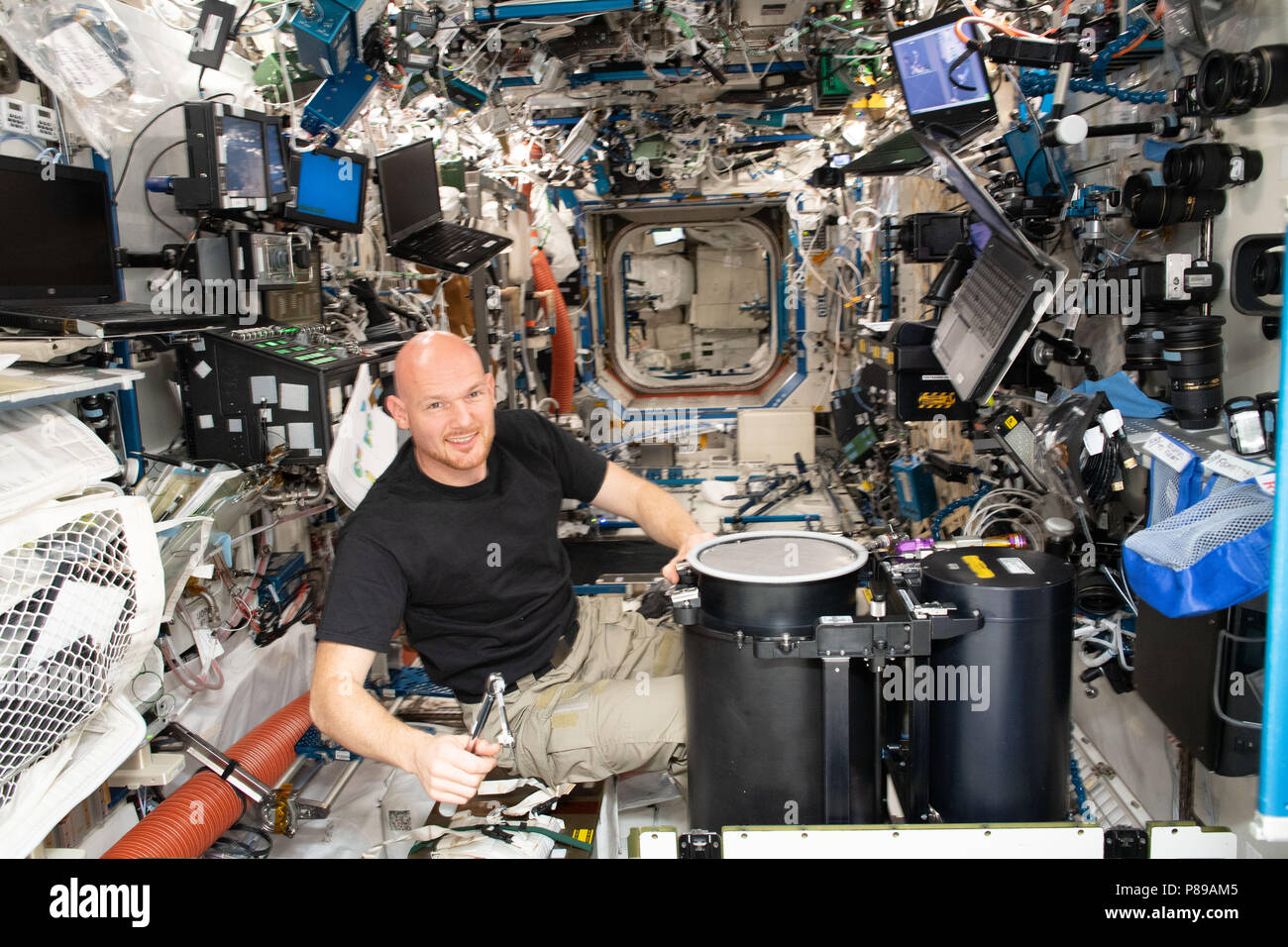 Expedition 57 crew member German astronaut Alexander Gerst of the European Space Agency works on life support maintenance inside the Destiny laboratory module aboard the International Space Station June 25, 2018 in Earth Orbit. - Stock Image