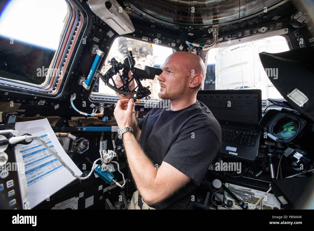 Expedition 57 crew member German astronaut Alexander Gerst of the European Space Agency calibrates and operates the Sextant Navigation device which is testing emergency navigation methods such as stability and star sighting in microgravity for future Orion exploration missions aboard the International Space Station June 28, 2018 in Earth Orbit. - Stock Image