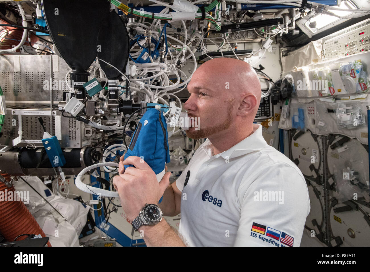 Expedition 57 crew member German astronaut Alexander Gerst of the European Space Agency exhales into an ultra-sensitive gas analyzer for the Airway Monitoring experiment aboard the International Space Station June 29, 2018 in Earth Orbit. - Stock Image