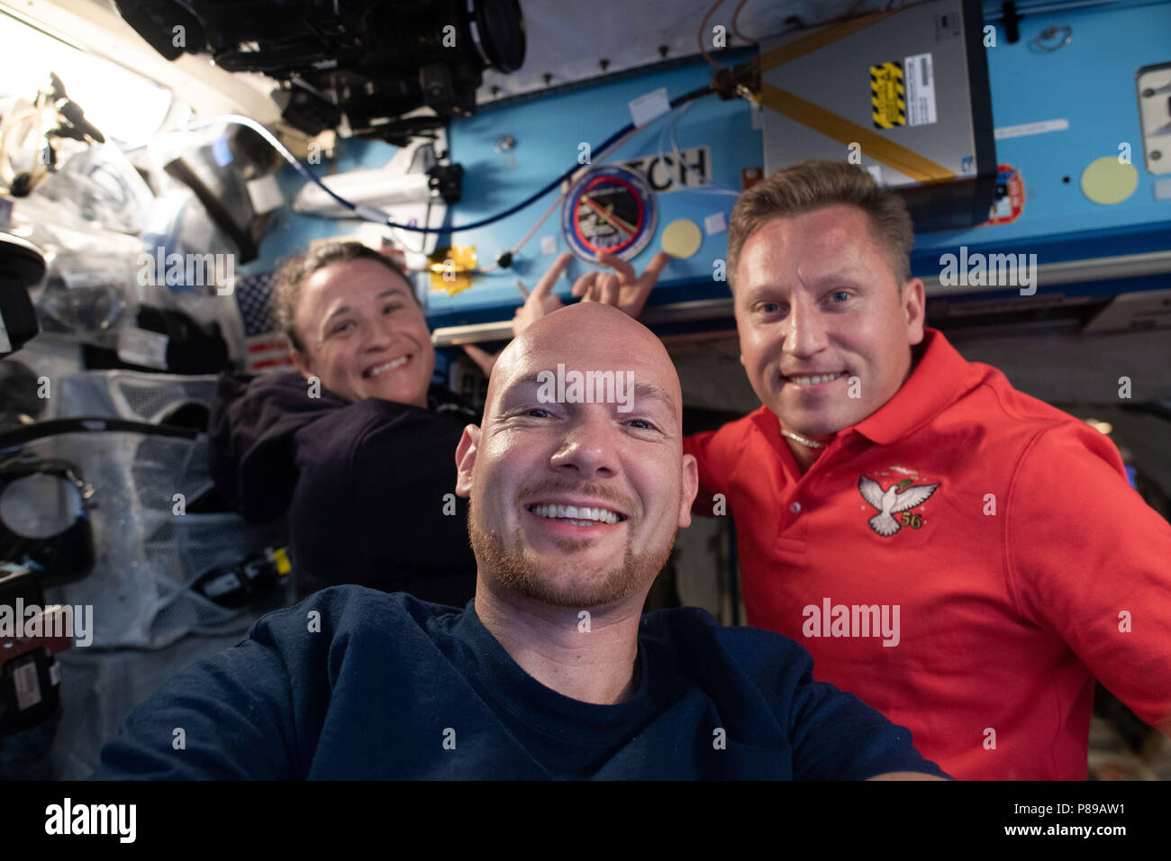 Expedition 57 crew members German astronaut Alexander Gerst of the European Space Agency, center, Serena Aunon-Chancellor of NASA, left, and Sergey Prokopyev of Roscosmos pose for a photo aboard the International Space Station June 23, 2018 in Earth Orbit. - Stock Image