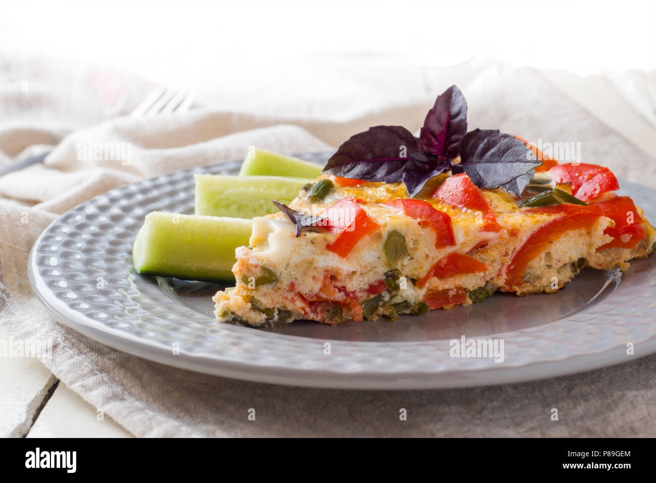 Omelet serving with vegetables on a plate on a white wooden table. - Stock Image