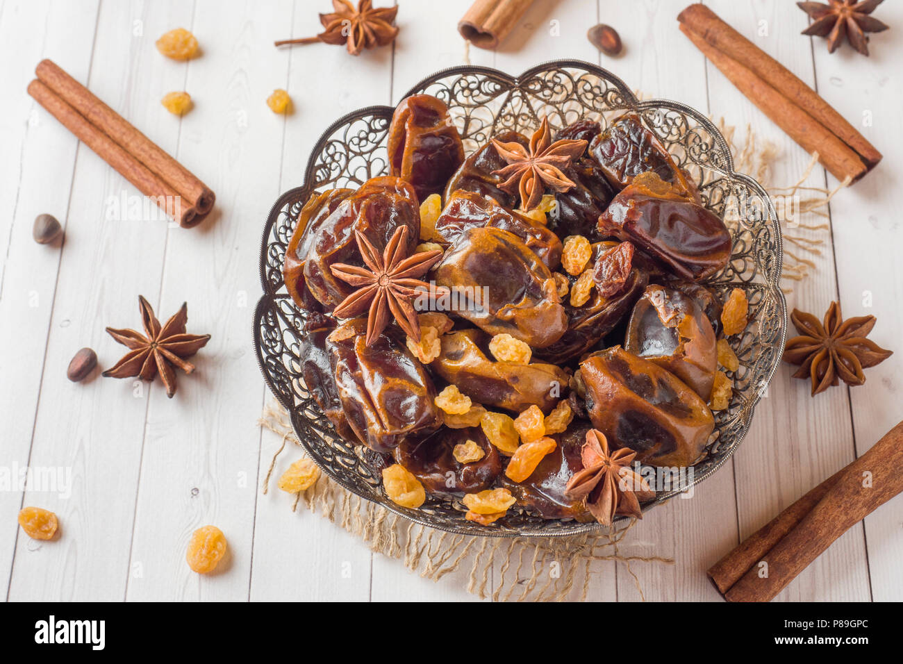 Oriental sweets, dried fruit dates and raisins, cinnamon and star anise in a plate. Turkish tea in glasses on a wooden background - Stock Image