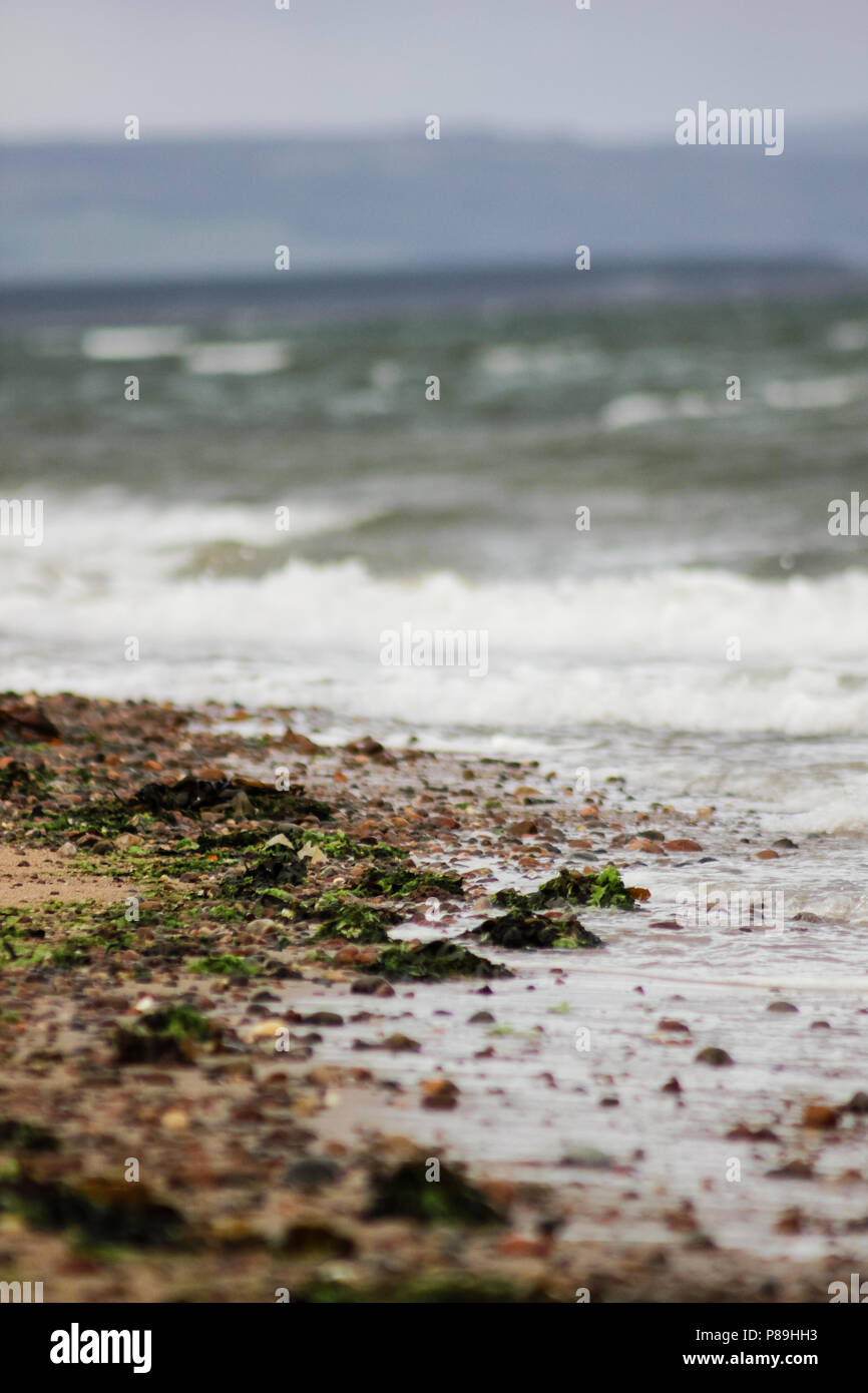 The tide breaks on a quiet beach near Nairn, Scotland. - Stock Image