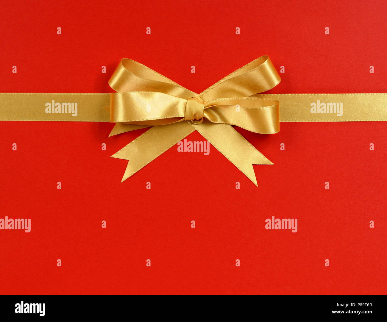 gold gift bow ribbon horizontal isolated on red wrapping paper
