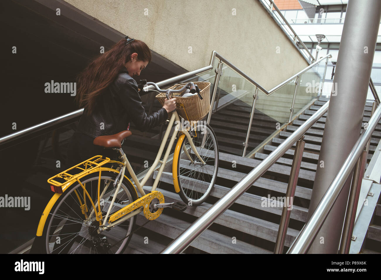 Woman with bicycle climbing up the stairs Stock Photo