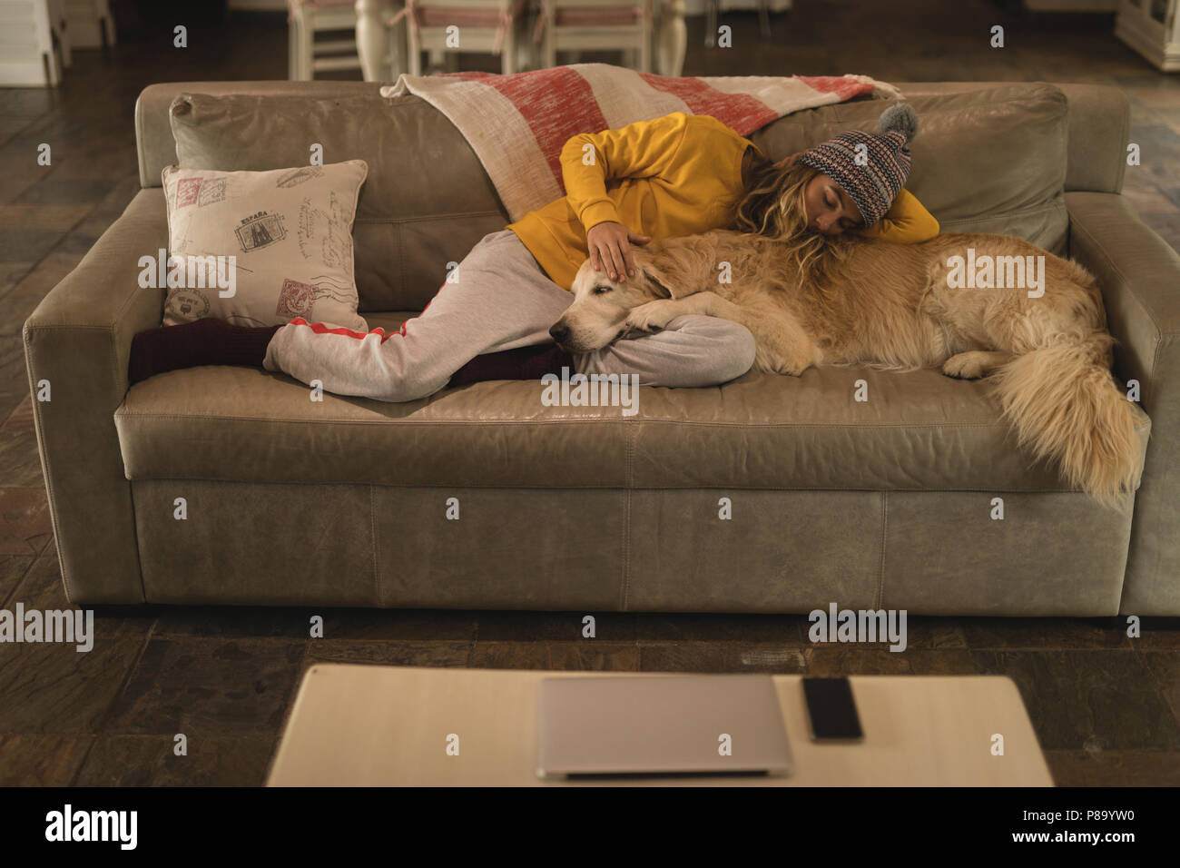 Girl with her dog sleeping in living room - Stock Image
