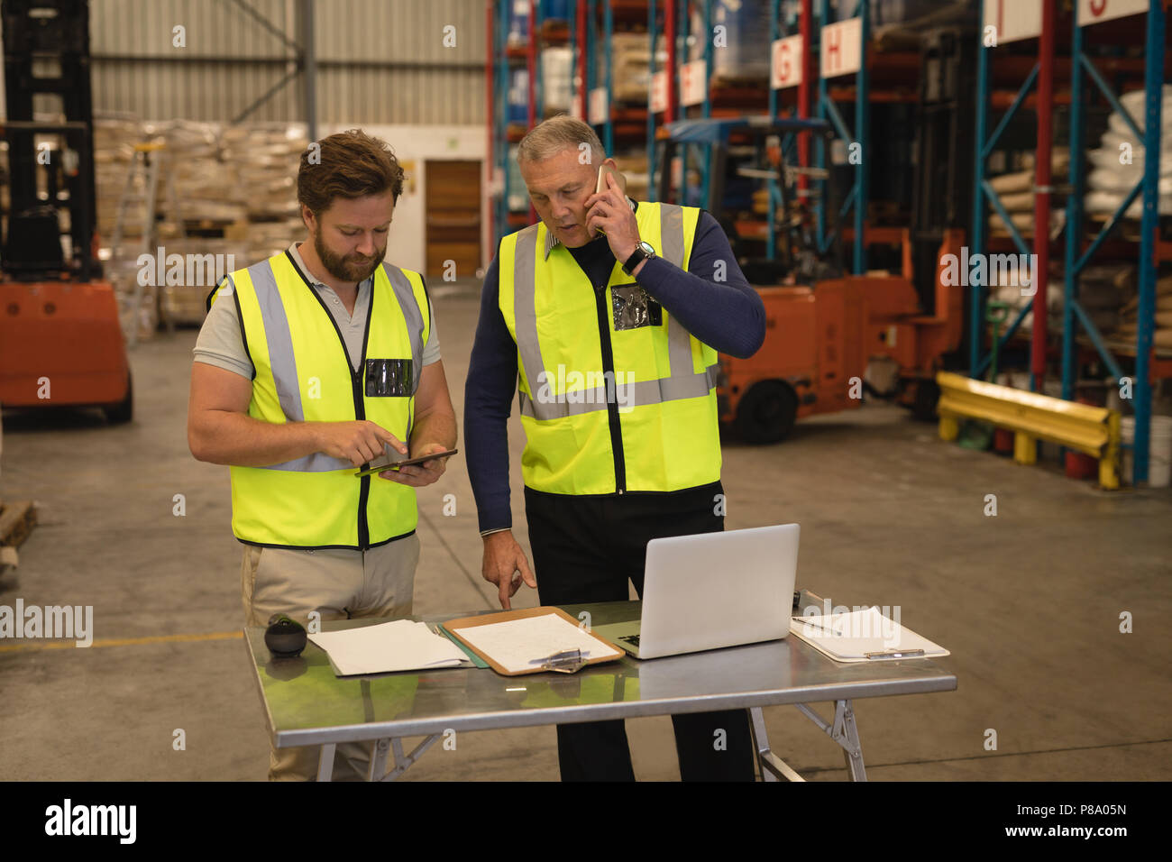 Male supervisors talking on mobile phone and using digital tablet - Stock Image