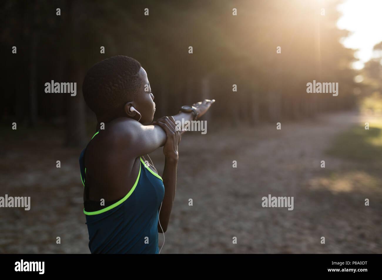 Female athlete doing stretching exercise - Stock Image