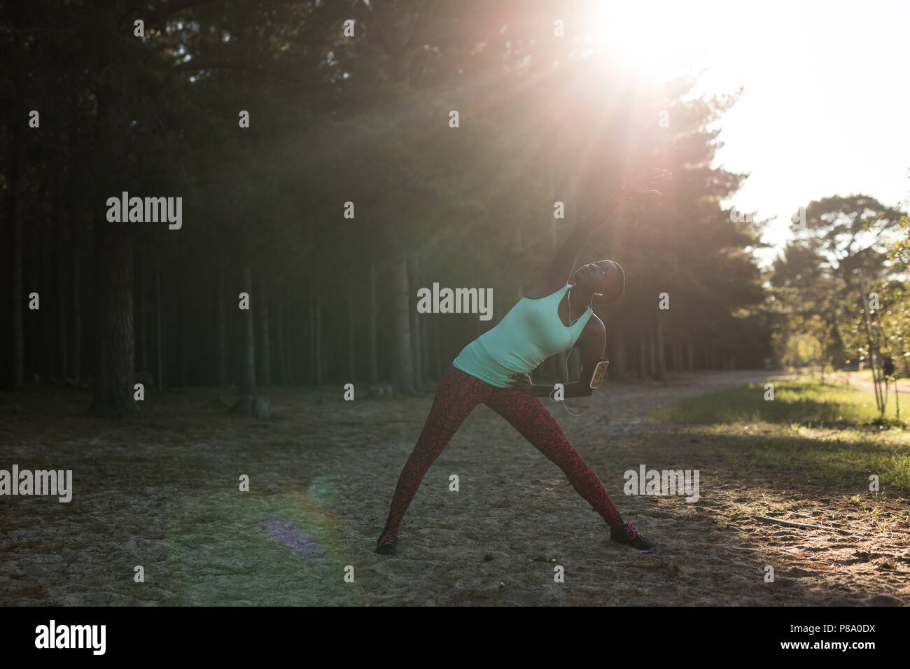 Female athlete performing stretching at morning - Stock Image