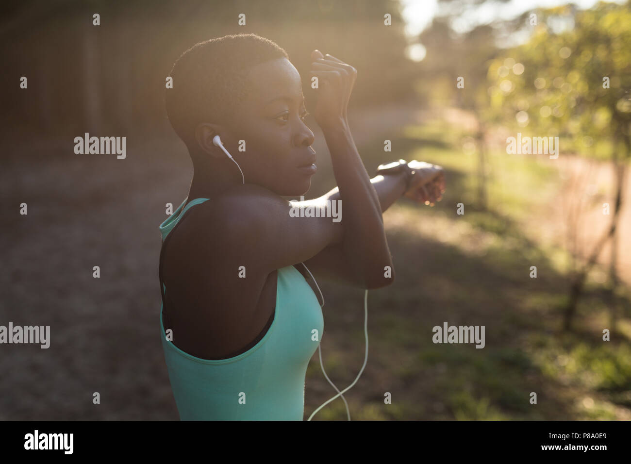 Female athlete listening to music while doing morning workout - Stock Image