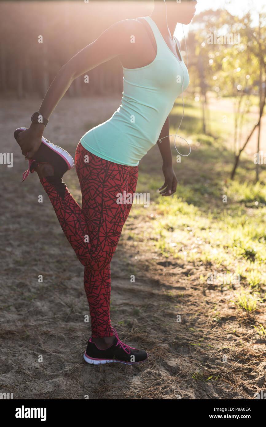 Female athlete doing leg exercise - Stock Image