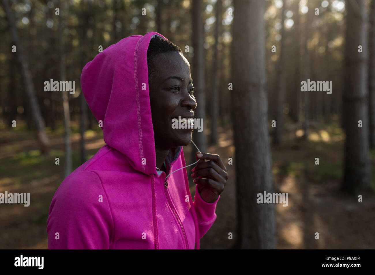 Female athlete in hooded jacket smiling in the forest - Stock Image