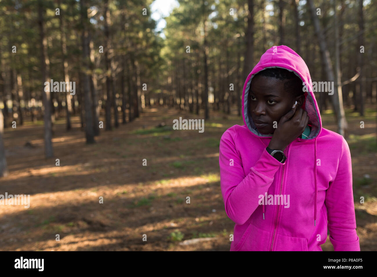 Female athlete in hooded jacket listening to music - Stock Image