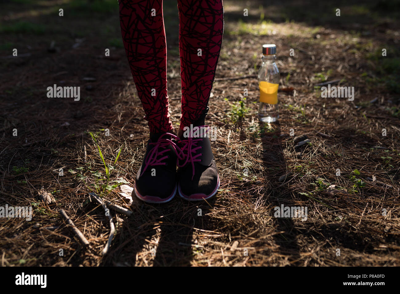 Female athlete wearing sneakers standing next to water bottle - Stock Image