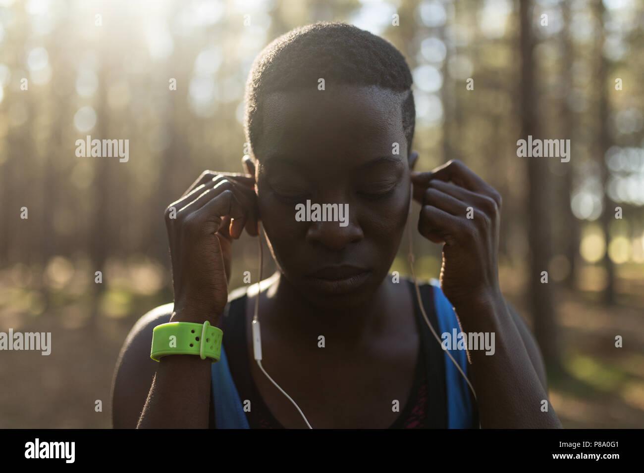 Female athlete listening to music in headphones - Stock Image