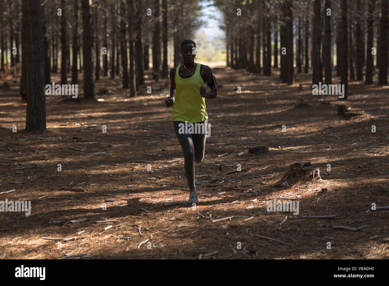 Female athlete jogging in the forest - Stock Image