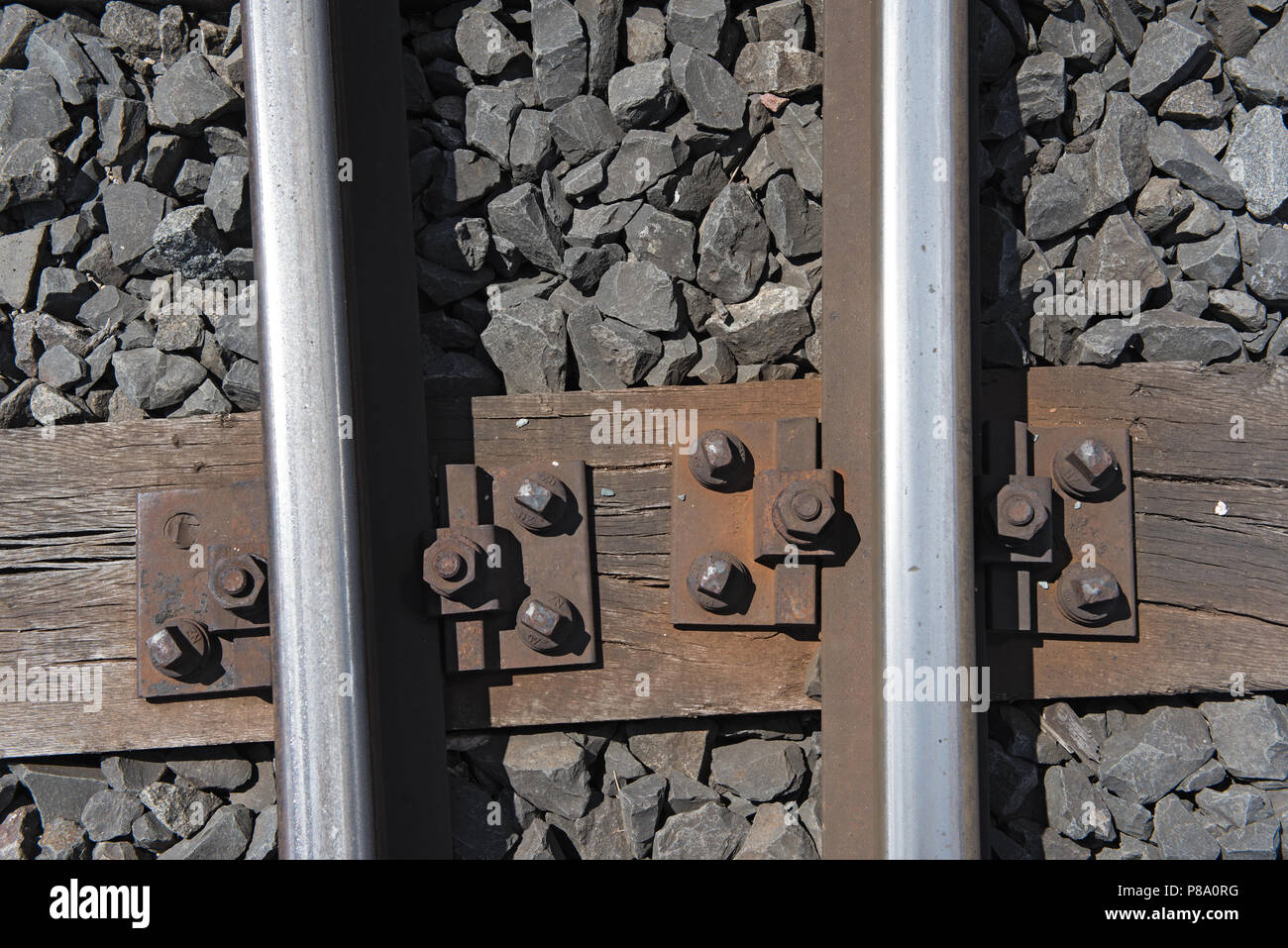Rails on the wooden sleepers with basalt stone as a substructure. - Stock Image