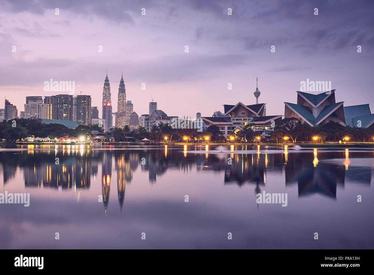 Moody sunrise in Kuala Lumpur in Malaysia. Reflection of the urban skyline in the lake. - Stock Image