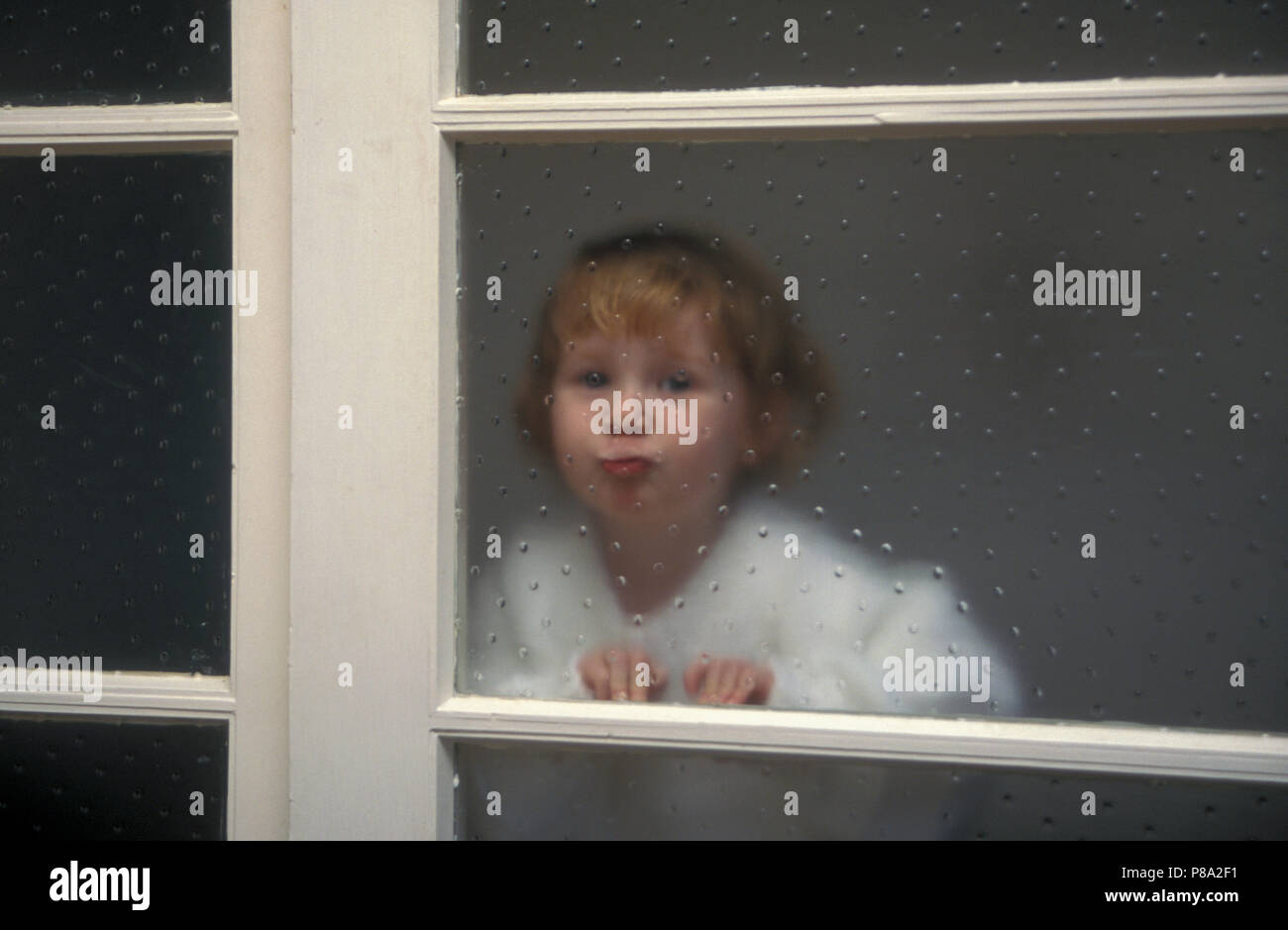 little girl pressing face against textured glass window - Stock Image