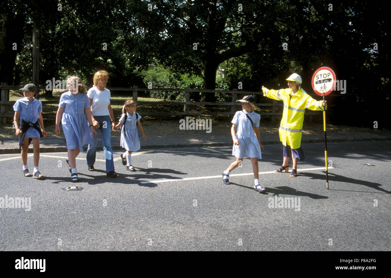Lollypop lady stopping traffic for school children to cross road - Stock Image