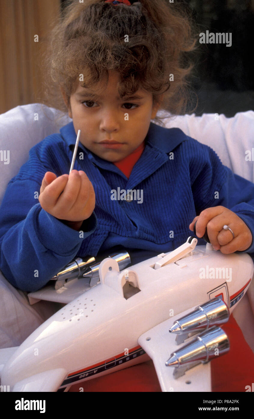 child playing with unsafe toy aeroplane - Stock Image