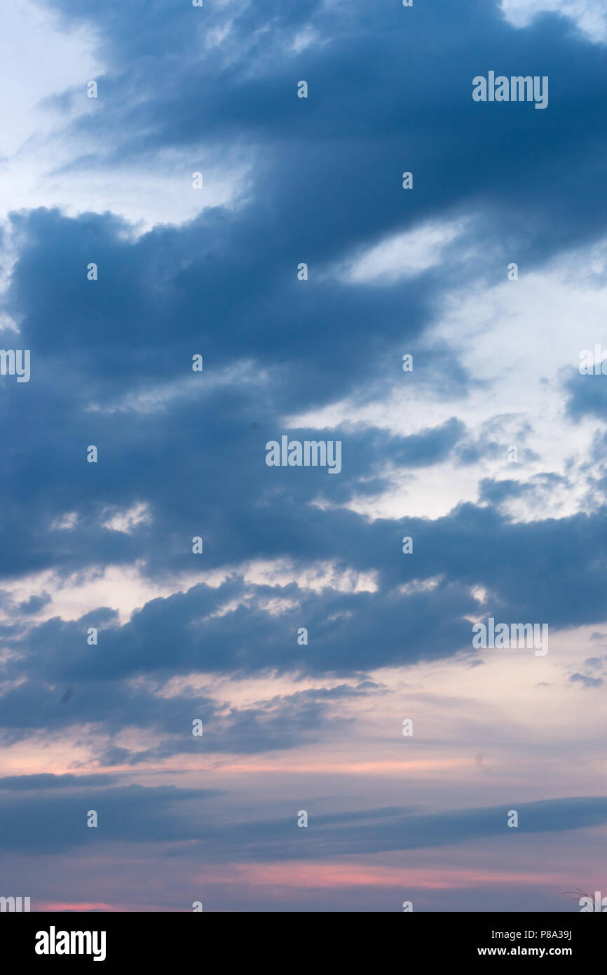Dark Blue Clouds Over A Light Blue Background With A