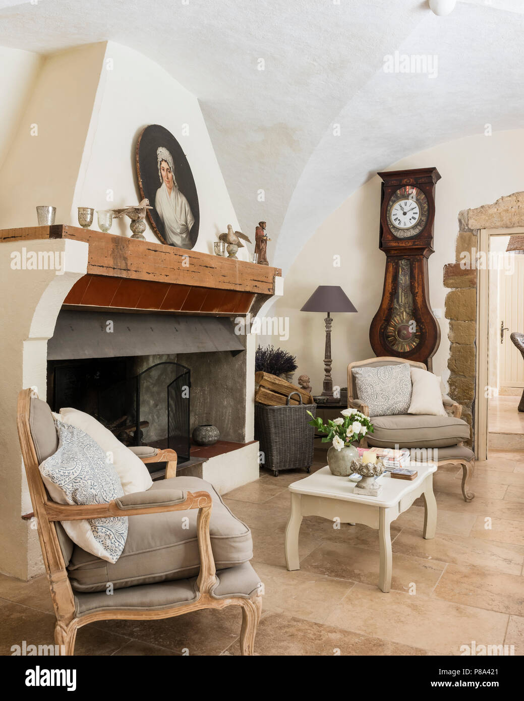 Vaulted ceiling  and upholstsred armchairs with antique clock - Stock Image