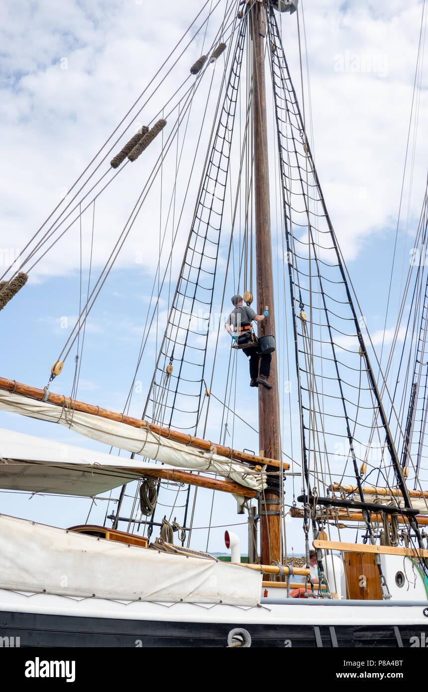 Sailor climbing the main mast of a sailing ship in the town of Marstal, Aero Island, Denmark Stock Photo