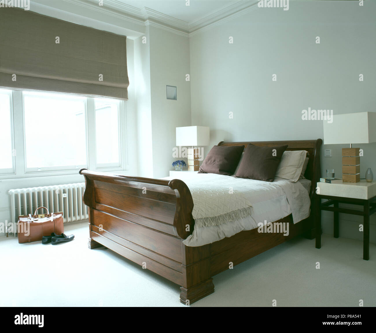 Lamps With Rectangular Shades On Tables Either Side Of Mahogany Sleigh Bed In Modern White Bedroom Stock Photo Alamy