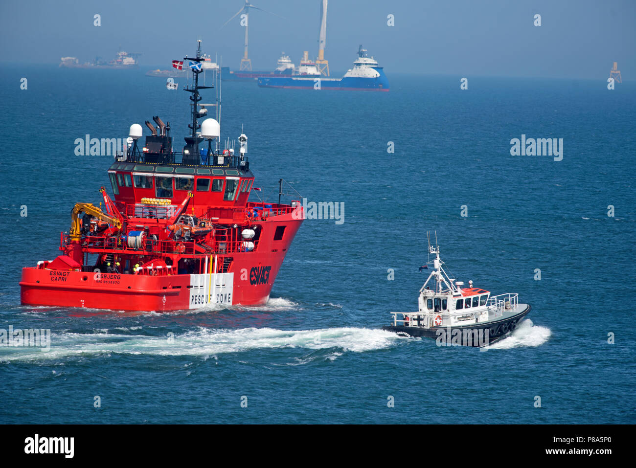Built in Singapore the Esvagt Capri makes its way out from Aberdeen harbour escorted by the local pilot boat till 1mile out. - Stock Image