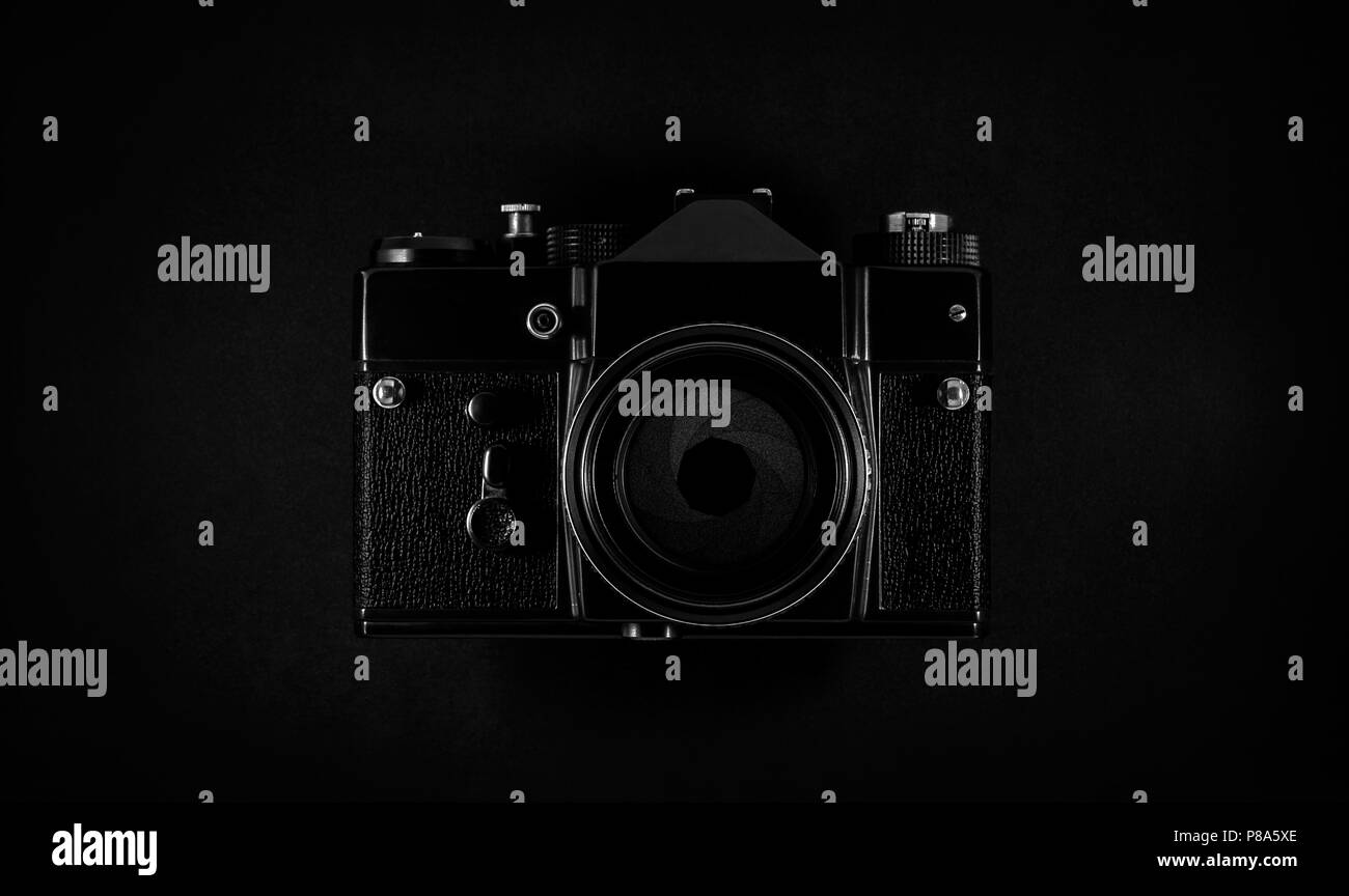 Old black SLR film camera with lens and aperture - Stock Image
