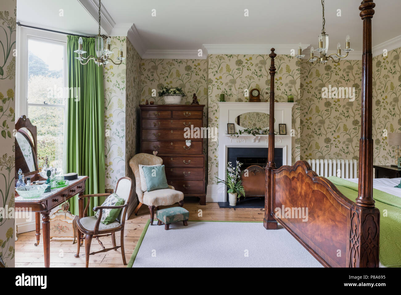 Antique wooden four-poster bed in Regency bedroom with tallboy and dressing table Stock Photo