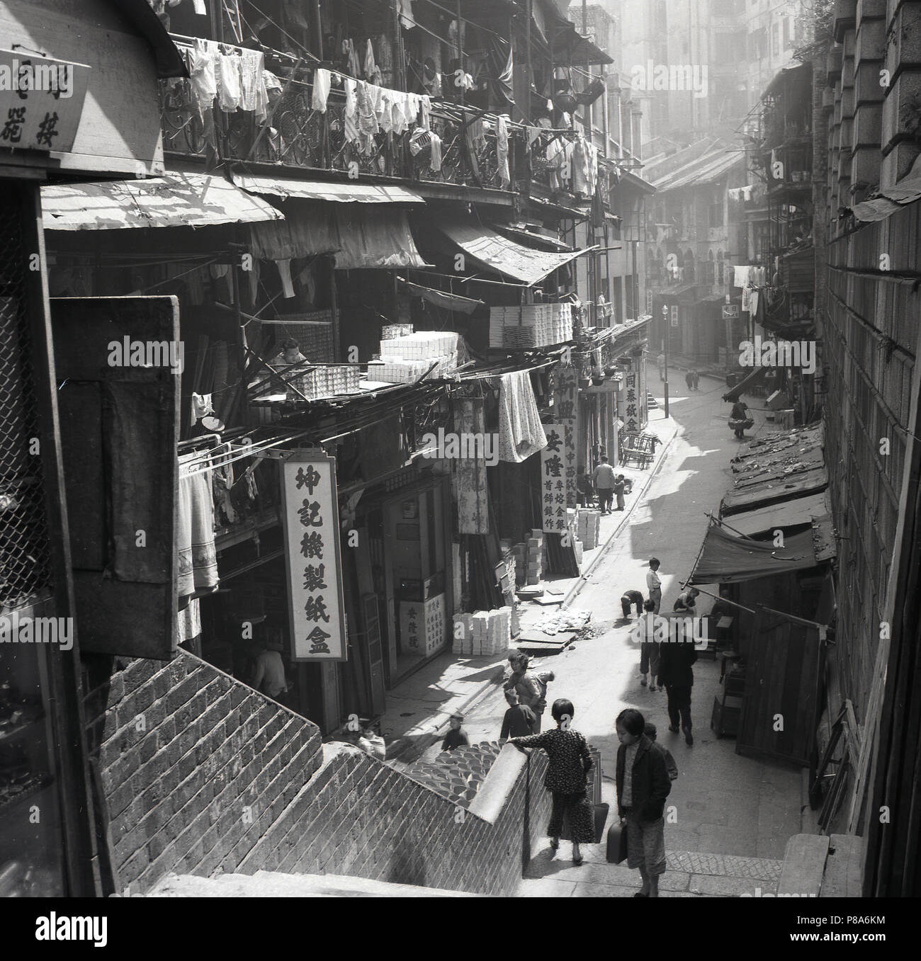 1950s, historical picture of an atmospheric narrow central Hong Kong  street showing the different levels of cramped living quarters above the shop units below, the original urban live-work concept now becomming popular in the west, abeit not on this scale and density. - Stock Image