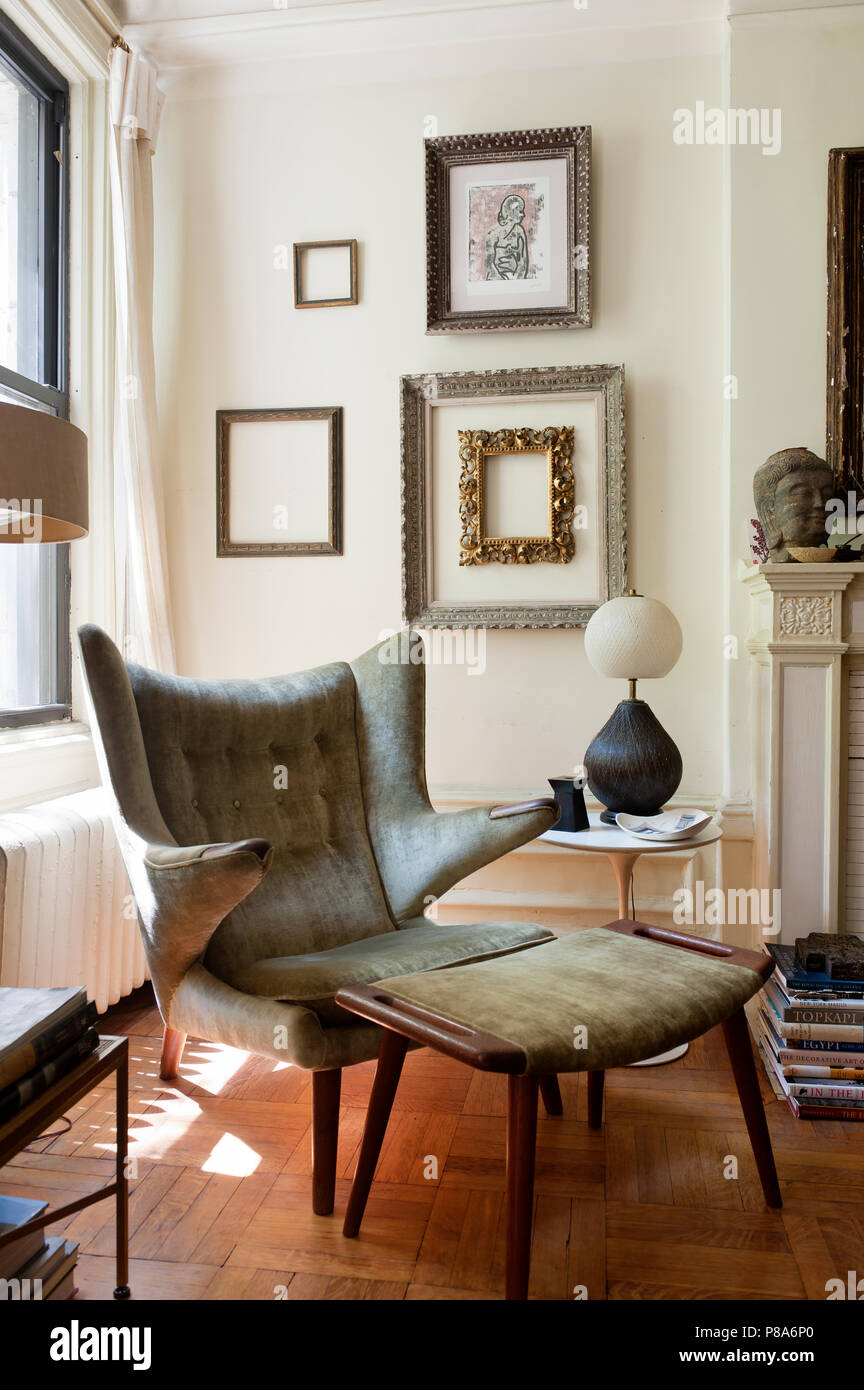 An original Papa Bear lounge chair designed by Hans Wegner in sitting room with decorative frames on the wall. - Stock Image