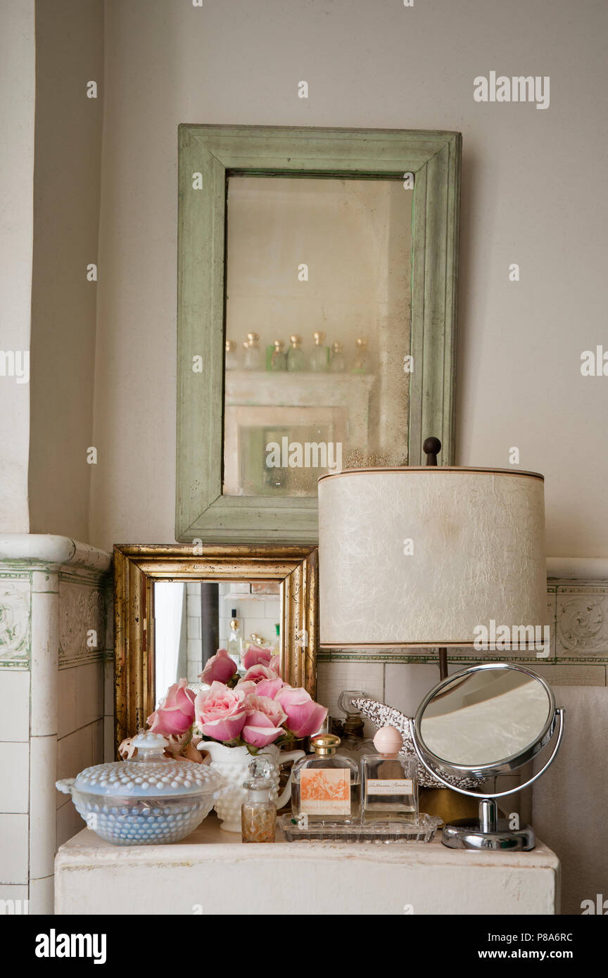 A selection of mirrors and perfumes on cabinet in shabby chic tiled bathroom - Stock Image