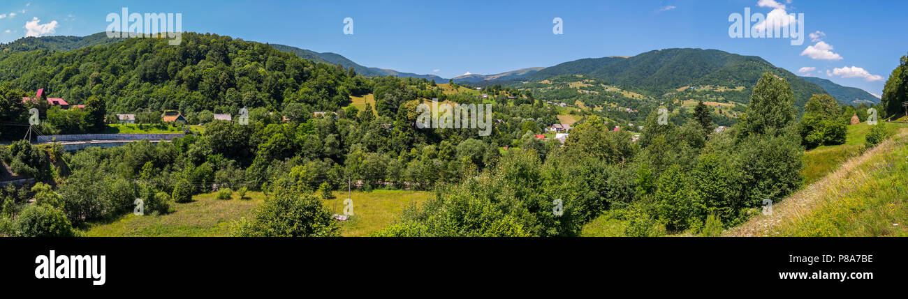 Beautiful panorama of the village stretched in a mountain valley and on the slopes covered with green trees under a cloudless summer sky. . For your d - Stock Image