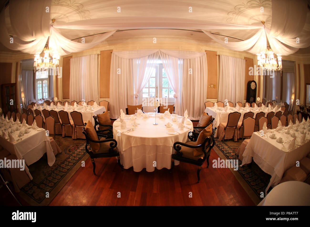 Seating layout of a wedding with the round bridal table in the centre of a colonial dining room with white sheer ceiling drapes, white tablecloths and... - Stock Image