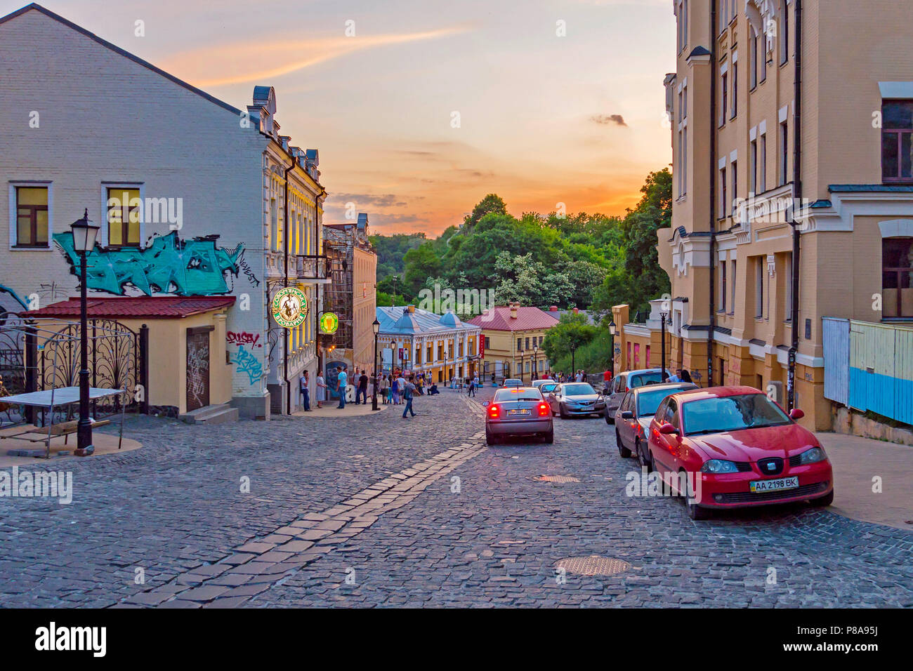 The wide street lined by a pavement goes down downtown Uzhgorod. Many tourists and city dwellers walk under the western sun . For your design - Stock Image