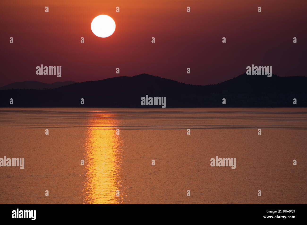 Orange sun setting over the silhouetted Sardonic Islands with the suns yellow reflection sitting on the Aegean sea, East Attica, Greece, Europe. - Stock Image