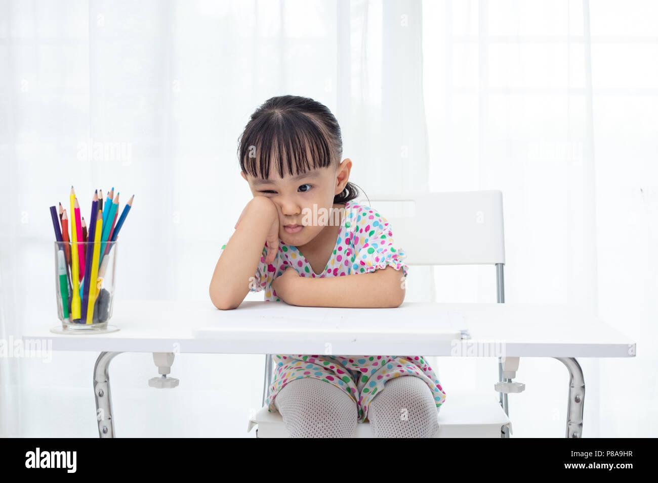 Asian Little Chinese girl doing homework at home - Stock Image