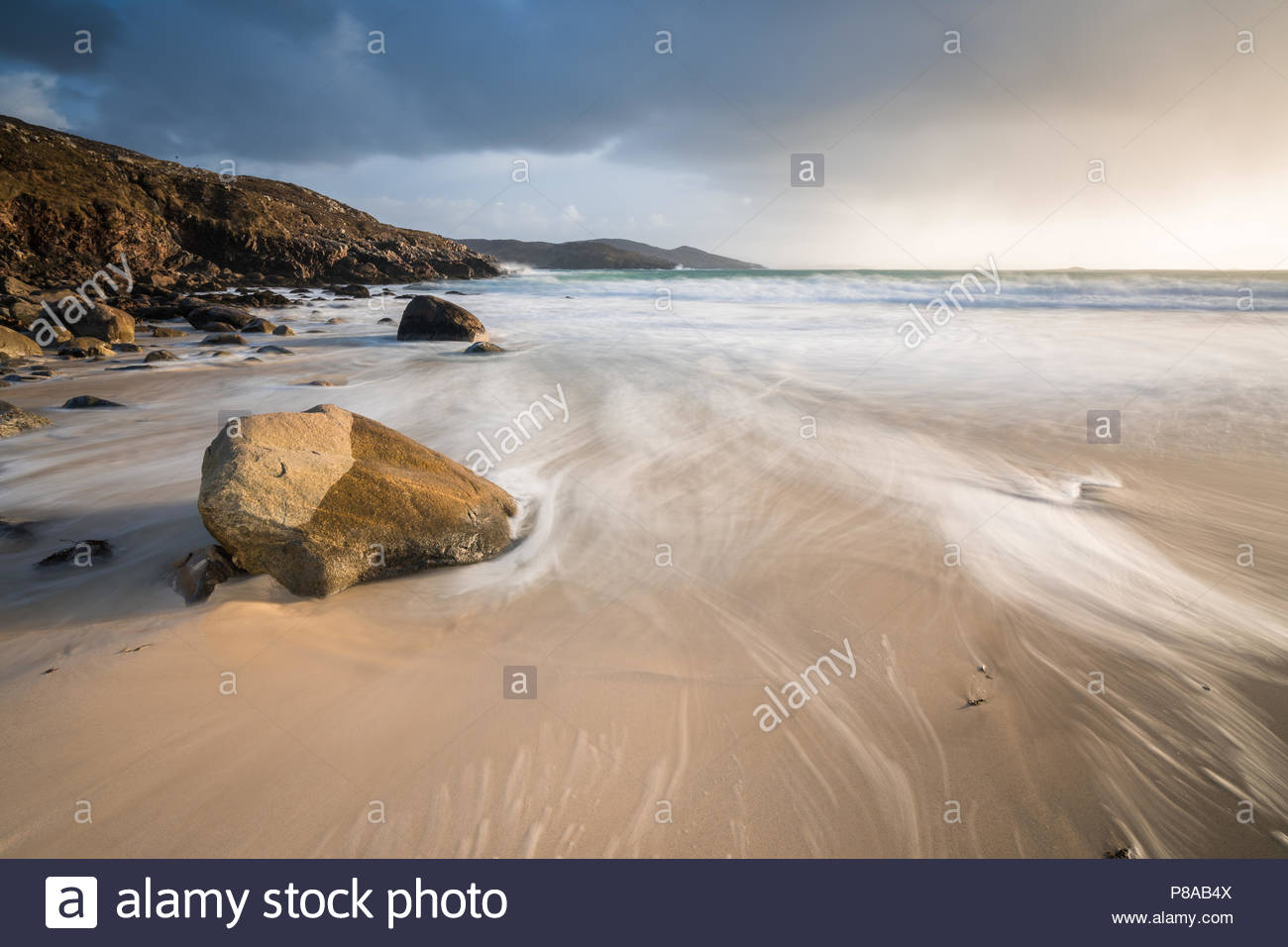 Fleeting but beautiful light passes in a changeable conditions at Hushinish on the Isle of Harris, one of the quieter beaches. - Stock Image