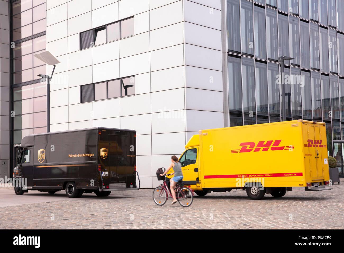 DHL parcel service and UPS parcel service cars in front of Crane House South at Rheinau harbor, Cologne, Germany.  DHL und UPS Fahrzeuge vor dem Kranh Stock Photo