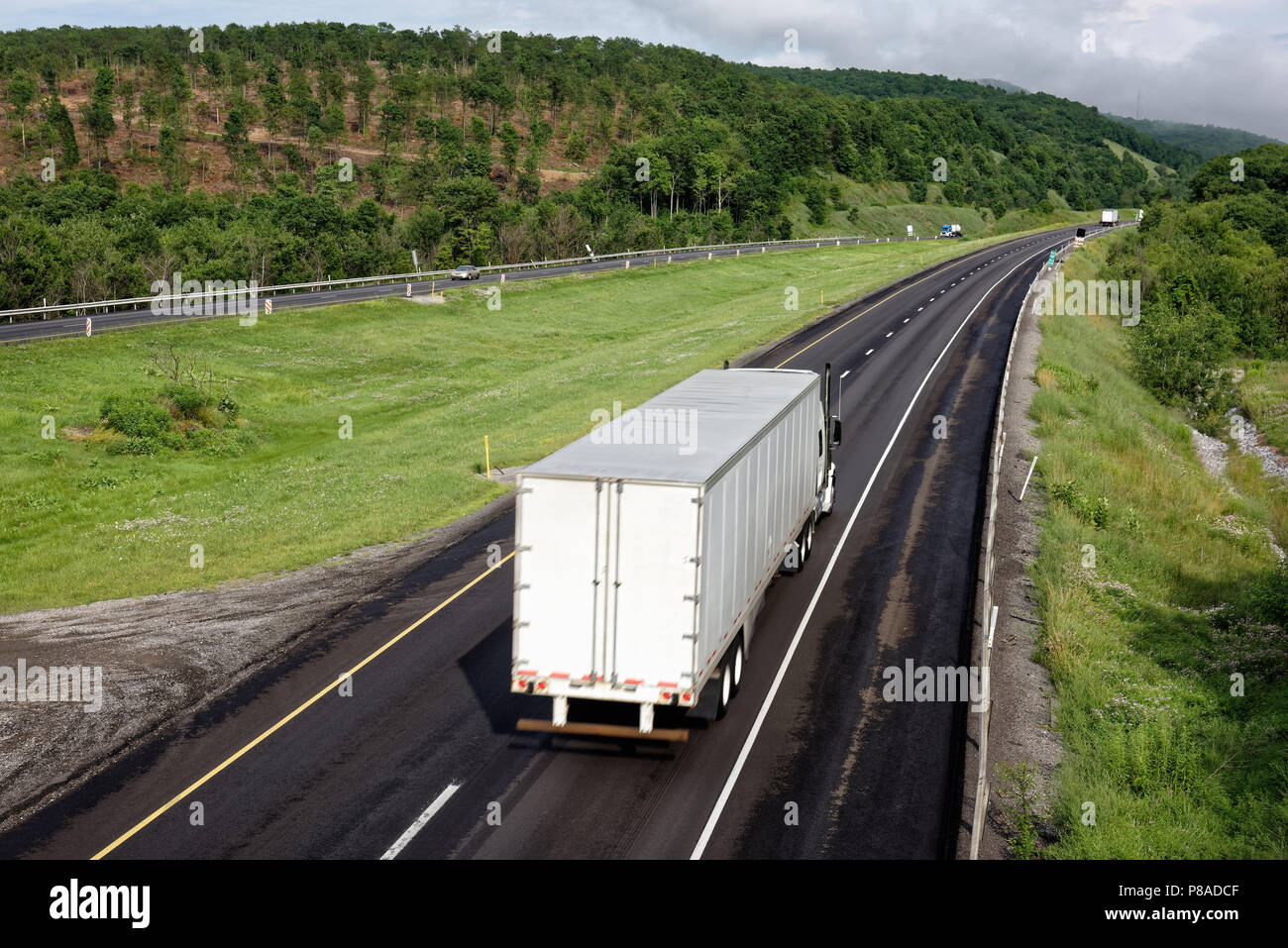 Trucks moving down interstate highway through scenic eastern mountains, tractor trailers in trucking industry hauling freight, some motion blur. - Stock Image
